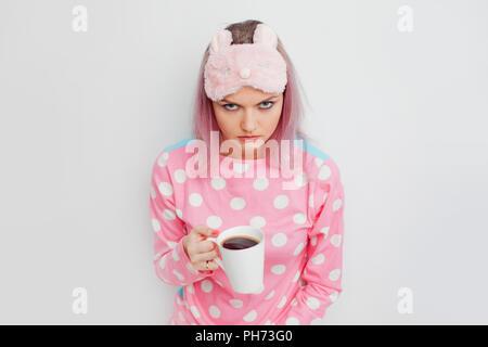 Fille malheureuse mal dormi. Portrait de femme grincheuse en pyjama rose. Blonde en un masque de sommeil, pas sommeil, insomnie. Banque D'Images