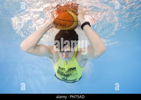 Adolescent jouant au basket-ball sous l'eau Banque D'Images