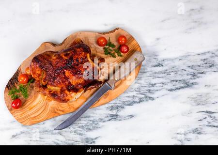 Grand poulet entier prêt à être servi sur planche de bois Banque D'Images