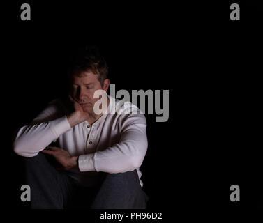 Homme mature montrant la dépression en restant assis dans l'obscurité Banque D'Images