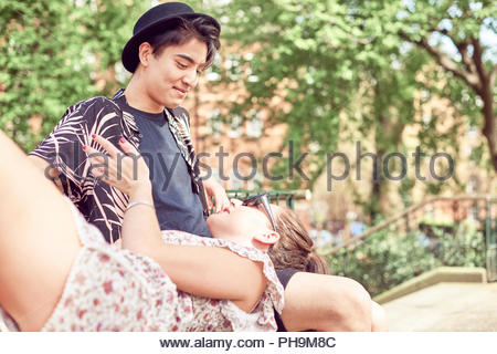 Teenage girl lying in boyfriend's lap à park Banque D'Images