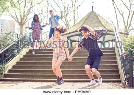 Teenage friends jumping down steps at park Banque D'Images