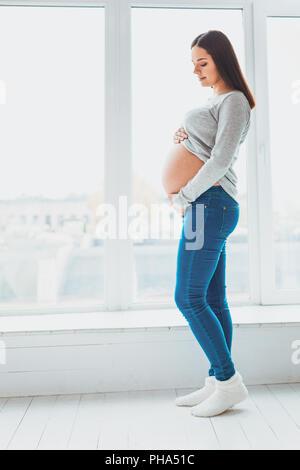 Expecting woman holding her baby bump debout dans la salle de séjour Banque D'Images