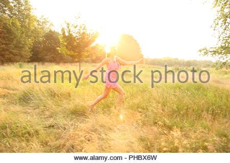 Jeune femme en robe rose tournant dans le champ Banque D'Images