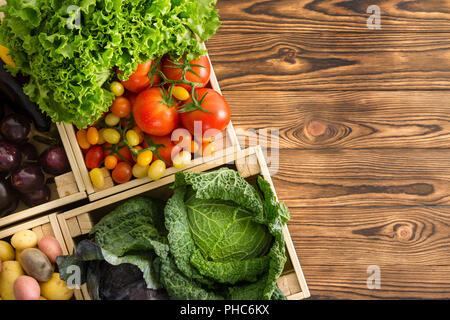 Variété de légumes frais et sain dans les cases affichées sur une table en bois table en bois à un marché de producteurs biologiques Vue descendante avec copie espace Banque D'Images