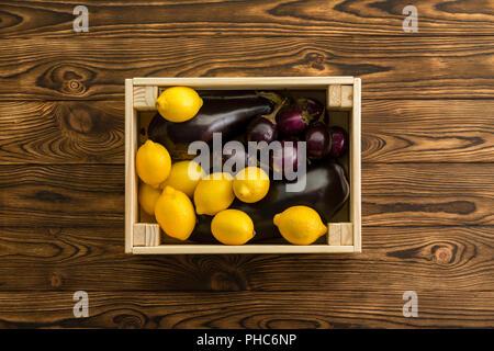Citrons jaune et violet couleur aubergine emballés ensemble dans une petite caisse en bois table en bois à un marché de producteurs biologiques centre vu de dessus Banque D'Images