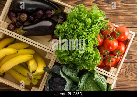 Un assortiment de légumes frais biologiques dans des caisses en bois sur l'affichage à un marché de fermiers vue close up d'en haut sur une table en bois rustique dans un régime alimentaire sain c Banque D'Images