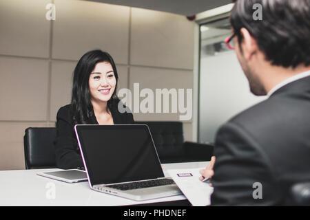 Belle jeune femme asiatique se présente à l'intervieweur avec grande sourit pour obtenir la création d'in office Banque D'Images