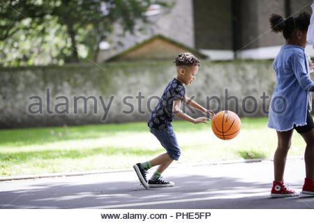 Garçon jouant au basket-ball in park Banque D'Images