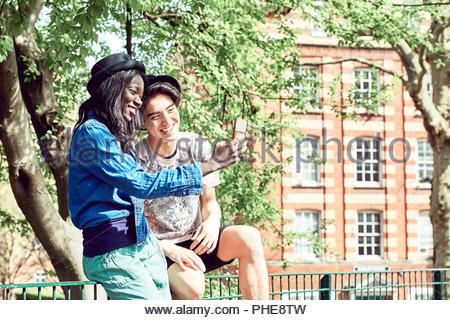 Couple en tenant en selfies parc Banque D'Images