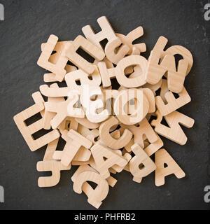 De nombreuses lettres en bois sur fond noir. Copier l'espace. Banque D'Images