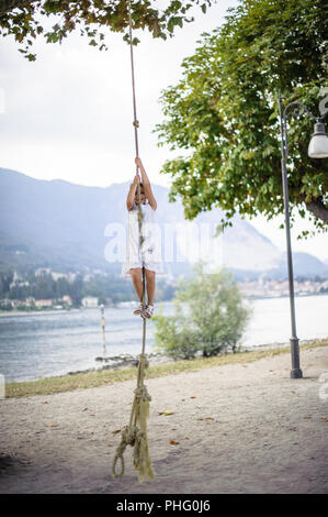 Petite fille grimpe sur une grosse corde dans la piscine en plein air Banque D'Images