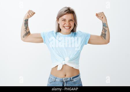 Montrez-moi du vrai pouvoir des muscles. Portrait de bon à la fois ludique et emotive girl avec bras tatoués, élever les mains et montrant les biceps en souriant largement, travaillant à la rose sur mur gris Banque D'Images