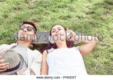 Teenage couple lying on skateboard at park Banque D'Images