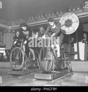 1940 femmes sur un vélo. Deux jeunes femmes sont les participants à un concours sur qui est d'atteindre la vitesse la plus élevée lors de l'équitation, le vélo sur une machine qui mesure. C'est la société norvégienne Gresvig qui est l'organisateur de l'événement. La société a été Norways plus grand fabricant de skis et vélos, et leur haut location était le modèle diamant. La Suède des années 40. Kristoffersson Photo AX21-8 Banque D'Images