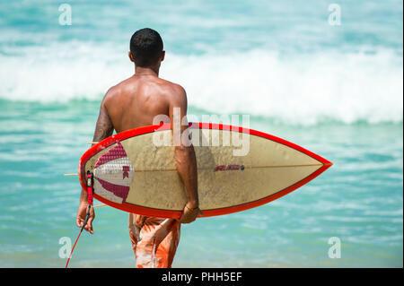 RIO DE JANEIRO - le 9 février 2017: jeune surfeur brésilien se promène avec son surf à travers les vagues à l'Arpoador, spot de surf populaire. Banque D'Images