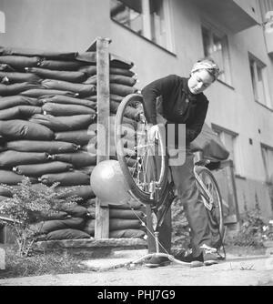 1940 femme sur un vélo. L'actrice suédoise Viveca Lindfors est la réparation de son vélo. Remarquez les sacs de sable placés en face de l'immeuble et l'entrée de l'abri de sous-sol. La Suède d'août 1940. Kristoffersson 159-32 Photo Banque D'Images