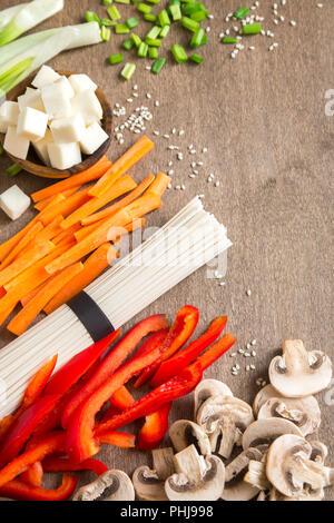 Végétalien végétarien ingrédients alimentaires asiatiques pour les sautés avec du tofu, les nouilles, les champignons et les légumes sur fond de bois avec l'exemplaire de l'espace. Banque D'Images