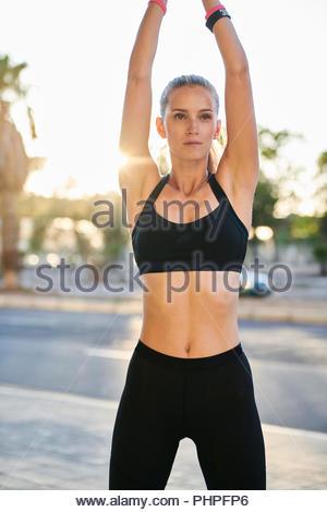 Woman wearing sports bra avec son bras levés Banque D'Images