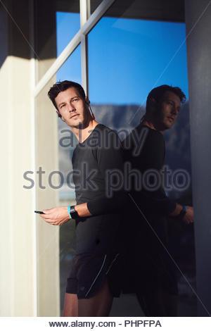 L'homme à l'aide de smart phone by window Banque D'Images