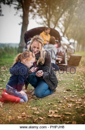 Mère et fille à l'aide de smart phone in field Banque D'Images