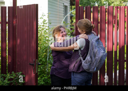 Belle femme d'âge mûr qui englobe les jeunes adultes dame et de rire, ils sont heureux de répondre après une longue séparation. Banque D'Images