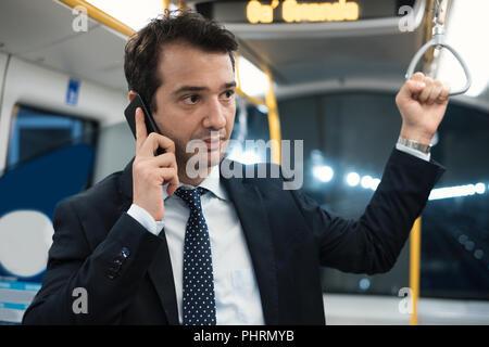 Portrait of businessman talking on son cellulaire pendant qu'il va au travail