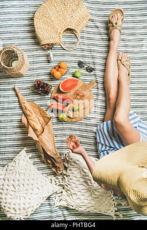 Pique-nique d'été. Jeune femme en robe rayée et la paille sunhat sitting avec verre de vin rose dans la main, des fruits à bord et baguette sur bla Banque D'Images