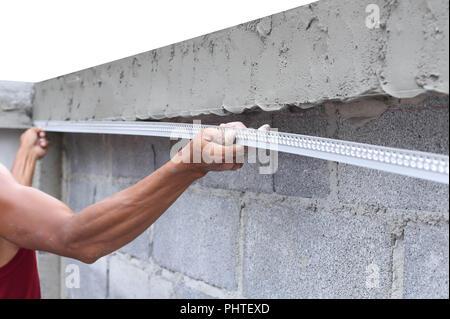 L'homme asiatique qui encadrent un mur de béton humide