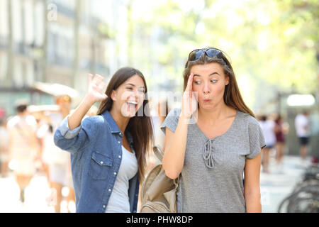 Message d'Happy teen en agitant la main et ami l'ignorant dans la rue Banque D'Images