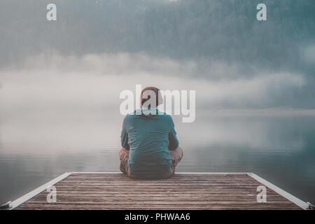 Jeune homme avec capuche assis sur la jetée d'un lac en un jour brumeux.