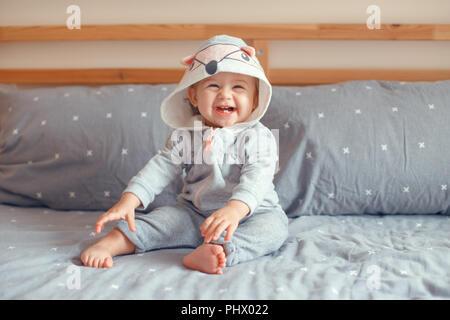 Portrait of cute adorable Portrait smiling baby girl blonde aux yeux bleus en pyjama gris avec fox hotte animal chat assis sur le lit dans la chambre. Natural