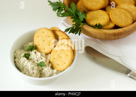 Snack de crackers et caillebotte La pâte de poisson aux herbes sur un fond clair. Focus sélectif. Banque D'Images