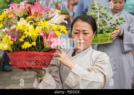 Nha Trang, Vietnam - Mai 5, 2018: une femme avec un panier de fleurs participe à la procession de la fête du temple de Po Nagar. Banque D'Images
