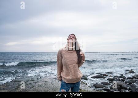 Cheerful babe debout à la plage sur un rock sauvage avec des vagues et l'eau bleu horizon dans l'arrière-plan. La liberté pour les gens aiment concept Mode de trav