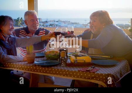 Deux groupes de personnes adultes senior Hommes et femmes s'amusant eatgin ensemble sur la terrasse du toit de la maison. soir Temps de célébration pour les personnes âgées Banque D'Images