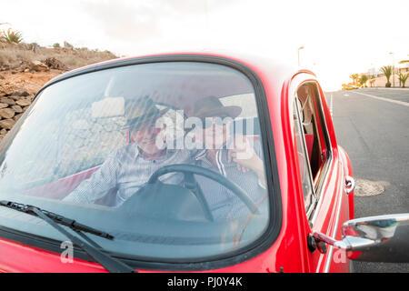 Joli couple hug et de l'amour à l'intérieur d'un vieux millésime rouge voiture garée sur la route. sourit et s'amuser voyageant ensemble. Le bonheur et le mode de vie pour le ni Banque D'Images
