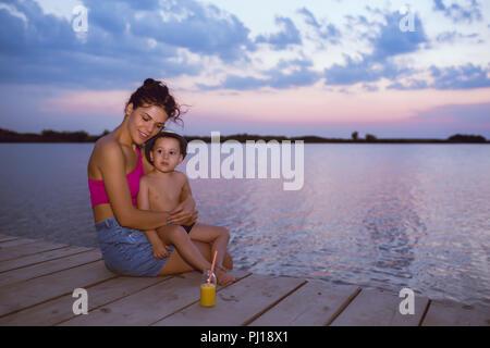 Mère heureuse avec son fils profiter du magnifique coucher du soleil tout en étant assis sur une jetée en bois par la rivière. Les émotions, les sentiments positifs, la joie. Famille heureuse Banque D'Images