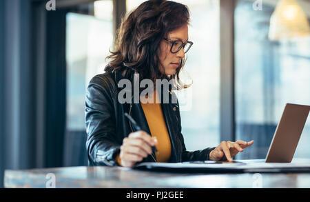 Businesswoman making notes sur un ordinateur portable au bureau. Femme entrepreneur assis à la table à écrire des notes tout en travaillant sur l'ordinateur portable. Banque D'Images