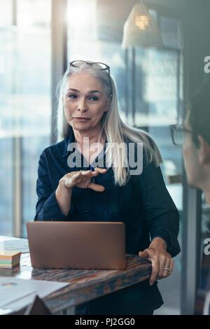 Femme d'âge mûr en réunion avec son équipe. Gestionnaire femelle d'une réunion avec ses collègues de bureau. Banque D'Images