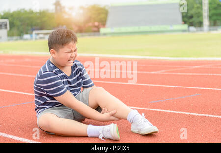 Garçon obèse la sensation de douleur après que sa douleur au mollet sur la piste, l'exercice de sport concept de dommage. Banque D'Images