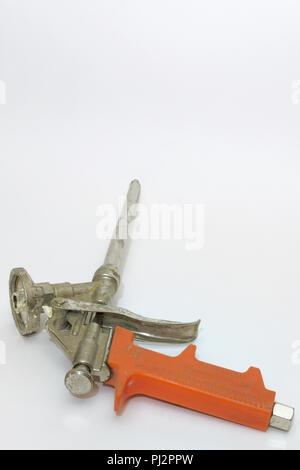 Pistolet à mousse de montage utilisé avec poignée en plastique orange Banque D'Images