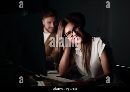 Young business woman assise à son bureau dans la nuit
