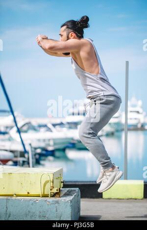 Athlète Fitness faisant sauter accroupi sur plyo-box de fortune sur mer pier Banque D'Images