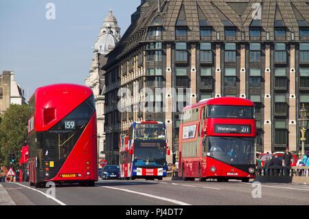 Une paire de nouveau Routemaster bus à impériale rouge passant sur le pont de Westminster. Banque D'Images