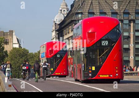 Vue arrière d'une paire de nouveaux Routemaster bus à impériale rouge passant certains cyclistes sur le pont de Westminster. Banque D'Images