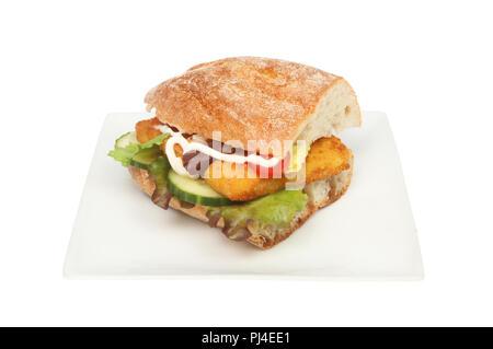 Les bâtonnets de poisson et de la salade dans un rouleau sur une assiette ciabatta isolés contre white Banque D'Images