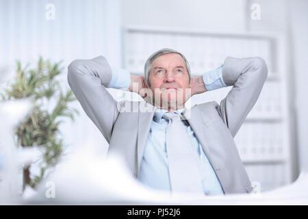 Senior businessman rêvant d'assis à son bureau Banque D'Images