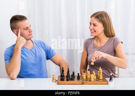 Jeune couple assis à la table et jouer aux échecs. Banque D'Images