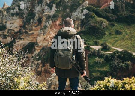 Un photographe ou un vidéaste ou voyageur avec un sac à dos et le trépied à la main choisit une belle vue à plus tard, faire de belles photos ou enregistrer des vidéos. Banque D'Images